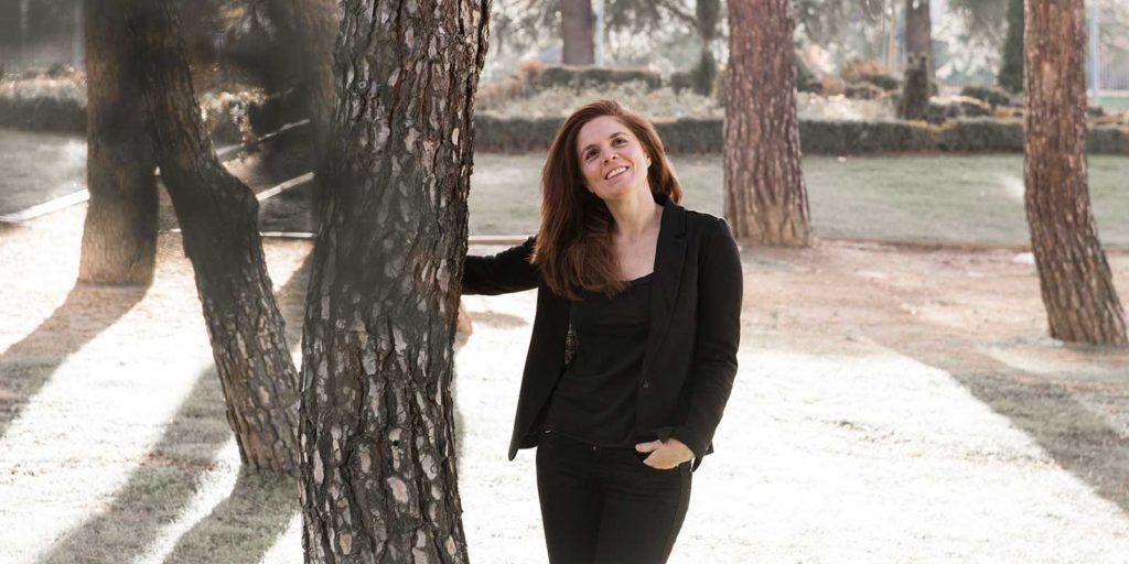 Áurea Vega en parque con pinos con traje negro
